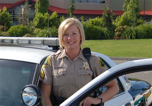 A blond female police officer standing in front of a car